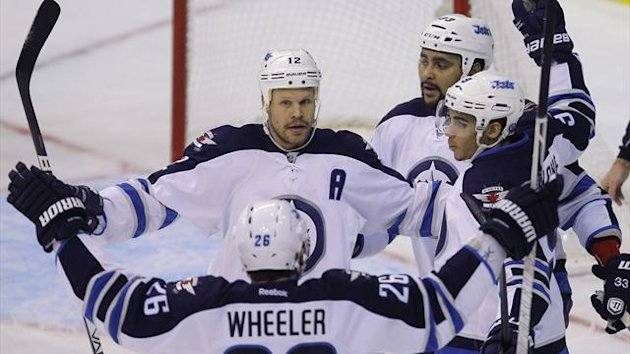 Winnipeg Jets celebrate with goal scorer Matt Kane (R) in the first period of their NHL hockey game against the Washington Capitals