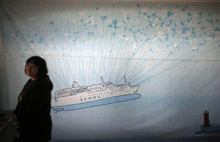 A woman stands in front of giant banner depicting capsized passenger ship Sewol during a candlelight vigil in Ansan