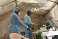 Health workers take blood samples for Ebola virus testing at a screening tent in the local government hospital in Kenema, Sierra Leone