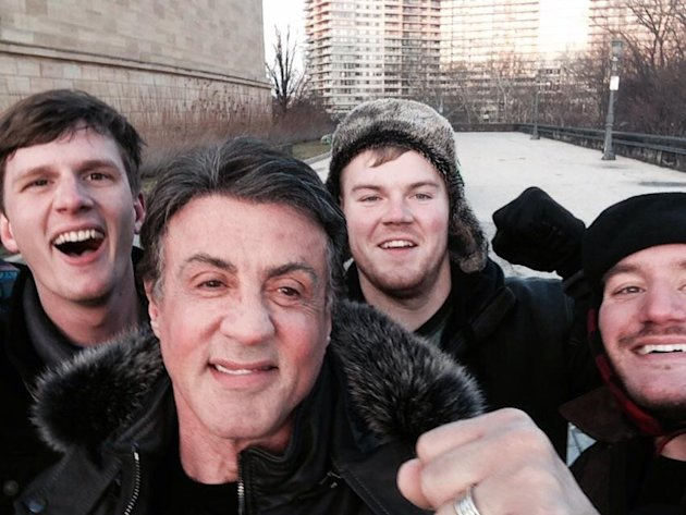 In this Jan. 17, 2015, photo provided by Peter Rowe, Rowe, right, takes a selfie with friends Jacob Kerstan, left, Andrew Wright, third from left and actor Sylvester Stallone in Philadelphia. Rowe said the three friends had just finished racing up the staircase at the city's Museum of Art when they saw Stallone. Stallone made the steps famous in his first turn as fictional boxer Rocky Balboa, who used them as part of his training regimen. Thousands of people now visit the steps each year to re-create the run. (AP Photo/Peter Rowe)