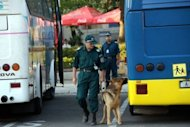 A Bulgarian policeman with a sniffer dog check for explosives buses after an explosion at Bourgas airport. An explosion ripped through a bus carrying Israeli holiday-makers in Bulgaria and killed at least six people on Wednesday in an attack the government in Israel blamed on arch foe Iran