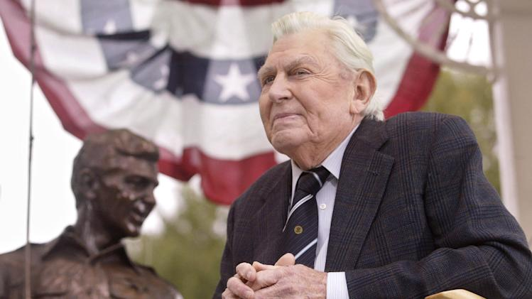 "FILE - This Oct. 28, 2003 file photo shows actor Andy Griffith sitting in front of a bronze statue of Andy and Opie from the ""Andy Griffith Show,"" after the unveiling ceremony in Raleigh, N.C.  Griffith, whose homespun mix of humor and wisdom made ""The Andy Griffith Show"" an enduring TV favorite, died Tuesday, July 3, 2012 in Manteo, N.C. He was 86. (AP Photo/Bob Jordan, File)"