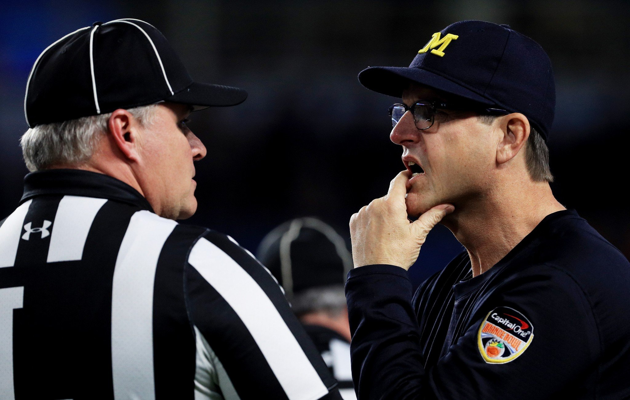 Is Michigan coach Jim Harbaugh talking to an official or pondering what he'll do in Italy? (Getty)
