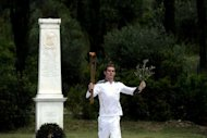 The first torch bearer, swimmer Spyros Gianniotis, runs with the Olympic flame during the lighting ceremony at Olympia, Greece, on May 10. The Olympic flame was lit in Ancient Olympia in Greece on Thursday, in a solemn ceremony filled with mystery and tradition that signals the final countdown to the start of this year's summer Games in London