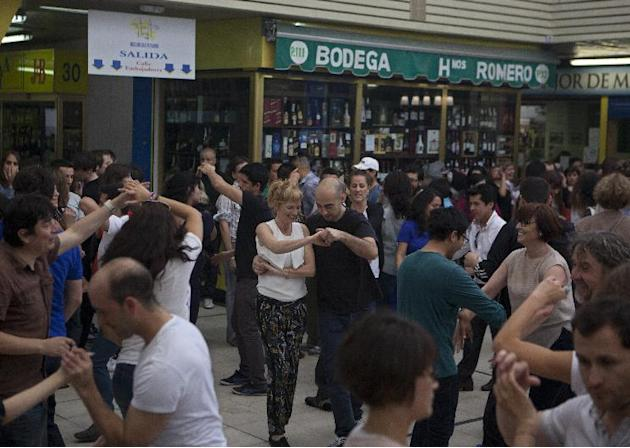 People dance in the San Fernando food market in Madrid, Spain, Sunday April 20, 2014. The traditional meat, fruit and vegetable market has undergone a transformation after various stalls closed down.
