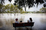 Two people sit on a bench surrounded by floodwaters after the Brisbane River broke its banks at West End in Queensland's state capital Brisbane on January 28, 2013. Deadly floodwaters were sweeping down Australia's east coast Tuesday, with Brisbane bracing for its river to peak as other towns waited anxiously as waters rose
