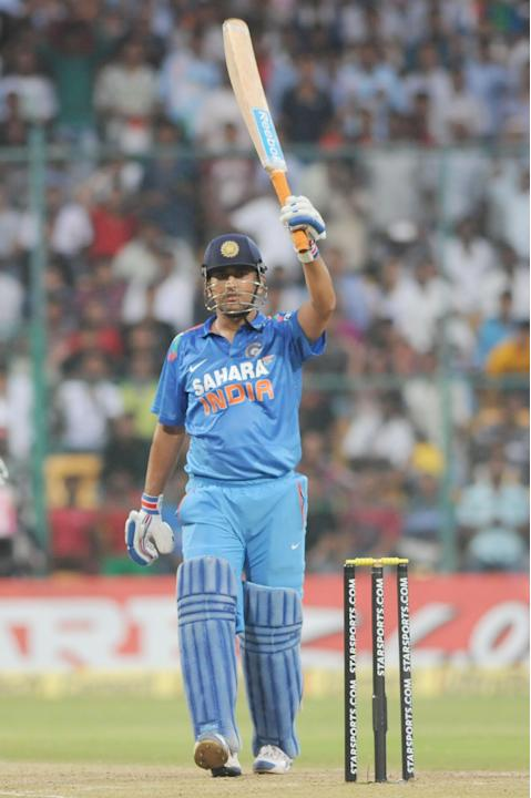 Indian captain M S Dhoni celebrates his half century during the 7th ODI between India and Australia played at Chinnaswamy Stadium in Bangalore on Nov.2, 2013. (Photo: IANS)