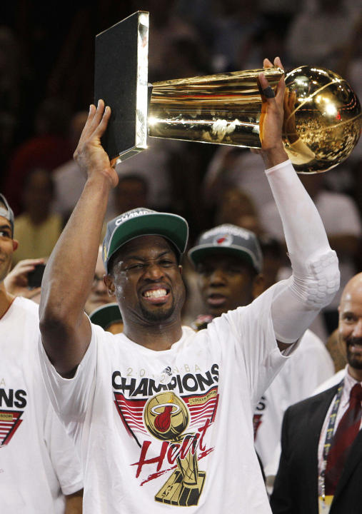 Miami Heat shooting guard Dwyane Wade holds the the Larry O'Brien NBA Championship Trophy after Game 5 of the NBA finals basketball series against the Oklahoma City Thunder, Friday, June 22, 2012, in