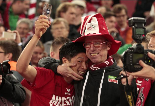 Cologne's Stoeger and Nagasawa celebrate victory against Bochum after the German second division Bundesliga soccer match in Cologne