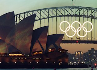 FILE - In this Sept. 14, 2000 file photo the Olympic Rings glow on the the Sydney Harbour Bridge the day before the opening of the 2000 Olympic Games in Sydney. The five massive rings from the Sydney Harbour Bridge that were the focal point of celebrations during the 2000 Olympics have been sold on eBay for 21,000 Australian dollars ($17,000). (AP Photo/Rob Griffith, File)