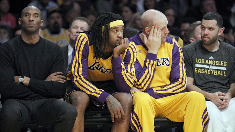 Los Angeles Lakers injured guard Kobe Bryant, left, center Jordan Hill, second from left, center Chris Kaman and guard Jordan Farmar, right, sit on the bench during the Milwaukee Bucks' 94-79 win in an NBA basketball game Tuesday, Dec. 31, 2013, in Los Angeles