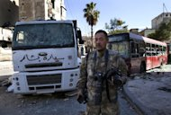 Japanese trucker Toshifumi Fujimoto stands in front of damaged buses in Aleppo's old city on December 27, 2012. He says he became a war tourist after getting bored with his humdrum job, a daily run from Osaka to Tokyo or Nagasaki hauling tanker loads of gasoline, water or chocolate