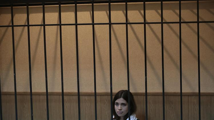 Nadezhda Tolokonnikova, a member of the feminist punk band, Pussy Riot, sits behind bars at a district court in Zubova Polyana 440 km southeast of Moscow in Russia's province of Mordovia, Friday, April 26, 2013. A Russian court is to consider whether one of the jailed Pussy Riot members is eligible for early release. Nadezhda Tolokonnikova, in custody since her arrest in March 2012, is serving a two-year sentence for the band's irreverent protest against President Vladimir Putin in Moscow's main cathedral. (AP Photo/Mikhail Metzel)