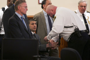 A court officer places handcuffs on the wrists of Aaron Hernandez. (AP)