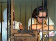 British grandmother Lindsay Sandiford (R) sits in a holding cell after her trial for drug trafficking in Denpasar, Bali on January 22, 2013. Drug syndicates are using Westerners to smuggle drugs into Bali, Indonesian authorities said as Sandiford became the latest to face the firing squad