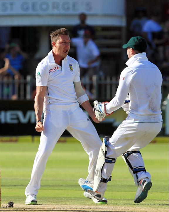 South Africa's bowler Dale Steyn, left, celebrates with teammate AB de Villiers, right, after dismissing Australia's captain Michael Clarke, left, for 1 run on the fourth day of their 2nd cric