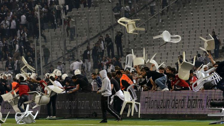 Besiktas fans throw plastic chairs onto the pitch during the Turkish Super League derby soccer match between Besiktas and Galatasaray in Istanbul