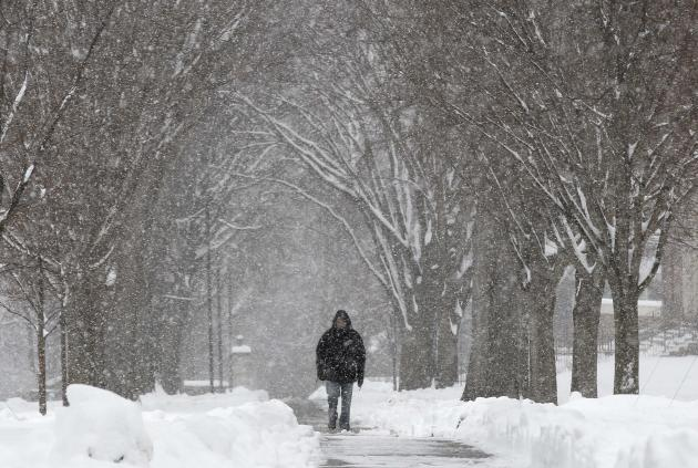 A pedestrian walks through the campus of Phillips Academy during a winter storm in Andover, Mass. Tuesday, March 19, 2013.  Winter went out with a blast in the Northeast on Tuesday, snow and sleet clo