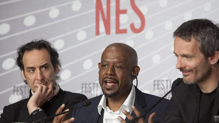 Actor Forest Whitaker, center, speaks during a press conference for the film Zulu at the 66th international film festival, in Cannes, southern France, Sunday, May 26, 2013. At left is composer Alexandre Desplat and director Jerome Salle. (AP Photo/Virginia Mayo)
