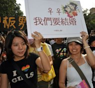 "File photo shows lesbians carrying a placard reading "" We want to marry"" during an annual gay parade in Taipei. Two women plan to tie the knot next month in Taiwan's first same-sex Buddhist wedding, as gay and lesbian groups push to make the island the first society in Asia to legalise gay marriage"