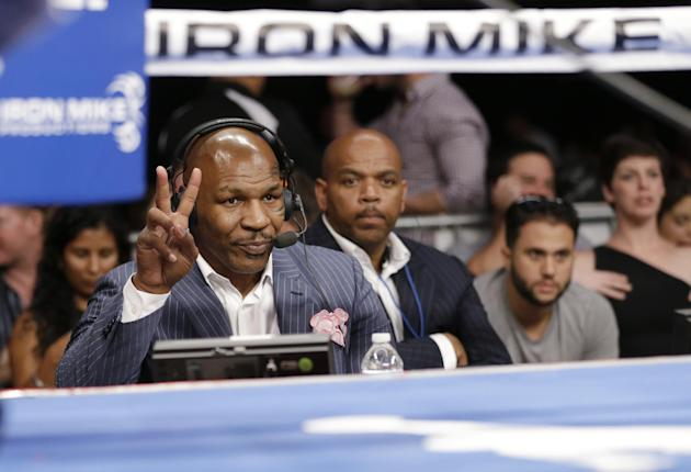 Promoter and former boxer Mike Tyson gestures as he wears a headset between boxing matches on Thursday, July 10, 2014, in Miami