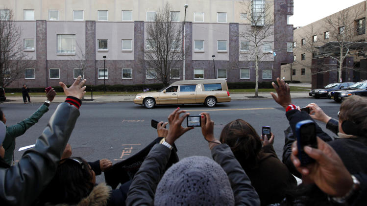 Fans wave as a hearse bearing the remains of Whitney Houston leaves the New Hope Baptist Church after the singer's funeral in Newark, N.J., Saturday, Feb. 18, 2012. Houston died last Saturday at the Beverly Hills Hilton in Beverly Hills, Calif., at the age 48. (AP Photo/Jason DeCrow)