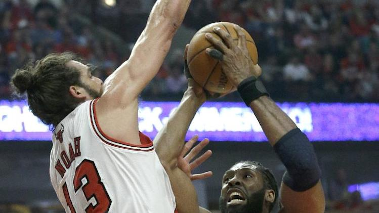 Washington Wizards forward Nene, right, drives to the basket against Chicago Bulls center Joakim Noah during the first half in Game 1 of an opening-round NBA basketball playoff series in Chicago, Sunday, April 20, 2014