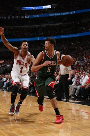 Michael Carter-Williams drives to the basket against Derrick Rose. (Gary Dineen/NBAE/Getty Images)