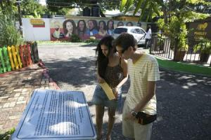 Tourists view a plaque dedicated to Bob Marley outside …