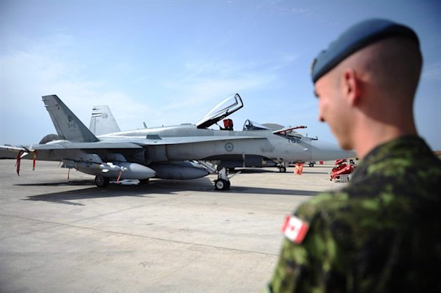 A Canadian soldier looks at a CF-18 at Camp Fortin in Trapani, Italy. (Canadian Press)