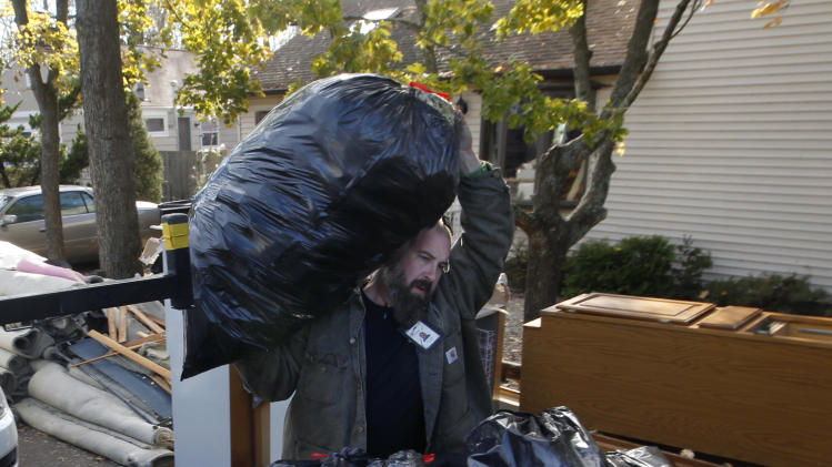 Jim Arasz, of Mount Laurel, N.J., carries trash bags of debris as he helps clean out a friends flood damaged home Tuesday, Nov. 6, 2012, in Brick, N.J., after the area suffered serious damage from last week's storm surge from Superstorm Sandy. Brick is ordering mandatory evacuations in advance of an approaching nor'easter.(AP Photo/Mel Evans)