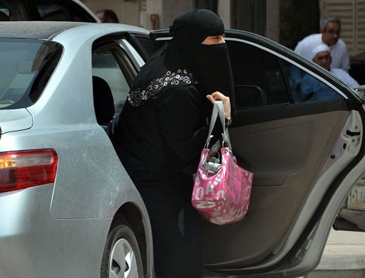 A Saudi woman gets out of a car after being given a ride by her driver in Riyadh. Denied the right to travel without consent from their male guardians and banned from driving, women in Saudi Arabia are now monitored by an electronic system that tracks any cross-border movements