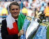 Manchester City's manager Roberto Mancini celebrates on the pitch with the Premier League trophy after their thrilling 3-2 victory over Queens Park Rangers, at The Etihad stadium in Manchester, on May 13. With their win, Man City secured their first league title since 1968
