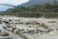 Residents salvage belongings from the Seti river near the Nepalese city of Pokhara on May 5, after their village was swept away in a flash flood. Rescuers scouring Nepal's central Annapurna region after severe flash flooding said Sunday that there was almost no hope of finding survivors and that the final toll could be as high as 60 dead