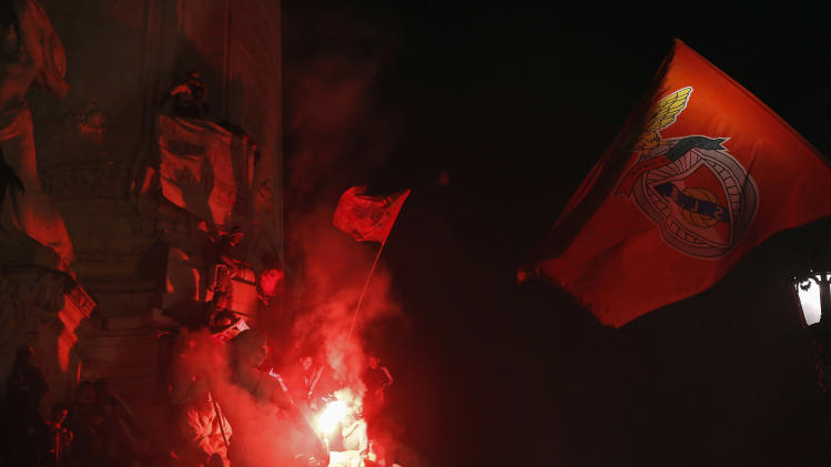 Benfica's supporters hold flags at the top of Marques Pombal statue after beating Olhanense and winning the Portuguese Premier League title, in Lisbon