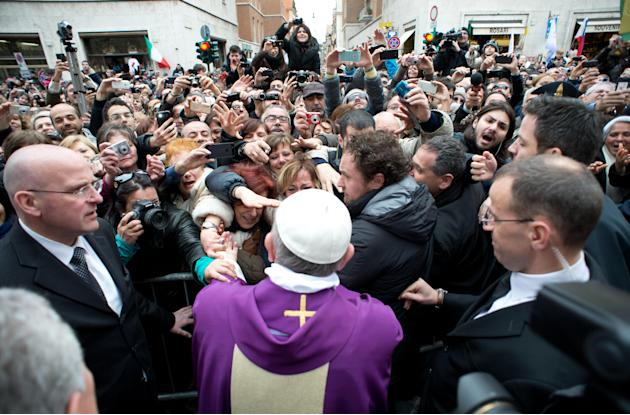 In this photo provided by the Vatican paper L'Osservatore Romano, Pope Francis greets faithful from a side gate of the Vatican, Sunday, March 17, 2013. Pope Francis began his first Sunday as pontiff b