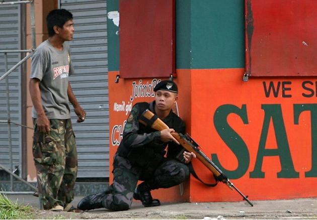 A police sniper gets into position to confront MNLF rebels in Zamboanga City in the Philippines on September 9, 2013