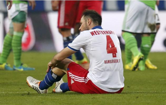 Hamburger SV's Westermann sits on pitch after German first division Bundesliga soccer match against VfL Wolfsburgin Hamburg