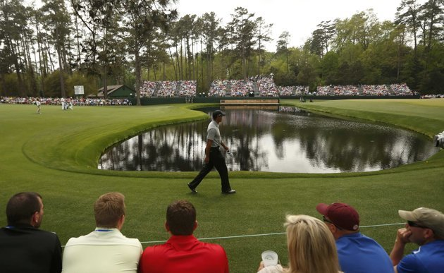 Tiger Woods of the U.S. walks to the 15th green during first round play in the 2013 Masters golf tournament in Augusta