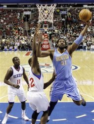 Denver Nuggets' Nene (31), of Brazil, goes up for a shot as Philadelphia 76ers' Elton Brand (42) and Jrue Holiday (11) defend in the first half of an NBA basketball game, Wednesday, Jan. 18, 2012, in Philadelphia. (AP Photo/Matt Slocum)