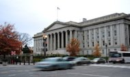 Vehicles drive by the US Treasury Building in Washington on November 15, 2011. Treasury Secretary Timothy Geithner has warned the nation will reach its $16.39 trillion debt limit on December 31.