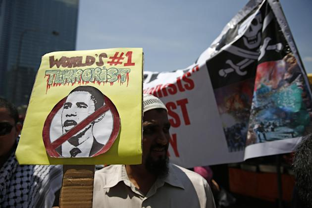 A Muslim activist holds the drawing of U.S. President Barack Obama during a protest condemning the trans-Pacific trade agreement ahead of President Obama's visit to Malaysia, outside the U.S. Emba