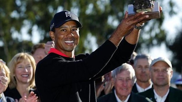 Tiger Woods holds up the trophy after winning at the Farmers Insurance Open in San Diego, California (Reuters)