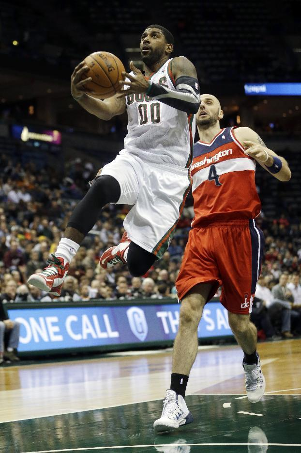 Milwaukee Bucks' O.J. Mayo, left, drives past Washington Wizards' Marcin Gortat (4) during the second half of an NBA basketball game Wednesday, Nov. 27, 2013, in Milwaukee. The Wizards won 100-92