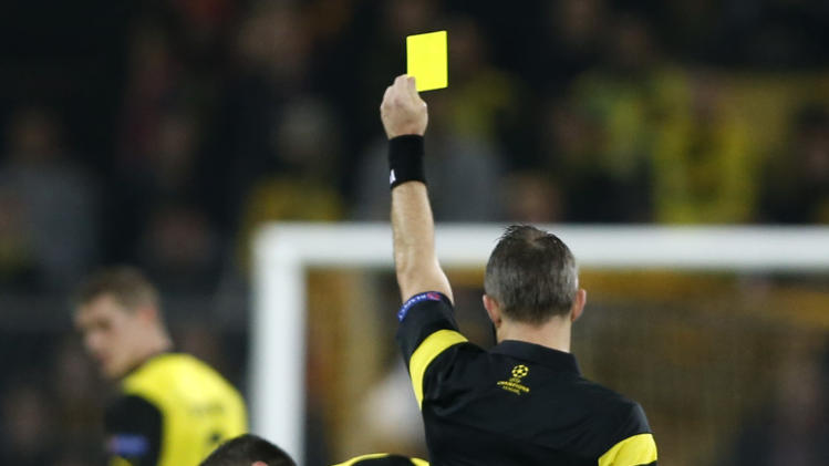 Borussia Dortmund's Lewandowski is shown yellow card during Champions League soccer match against Arsenal in Dortmund