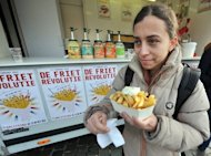 A woman eats fries with mayonnaise in Leuven, Belgium. Fries, crunchy, salty, tasty fried sticks of potato are claimed by Belgium and France as the product of their national gastronomic genius but the true origins are shrouded in popular folklore