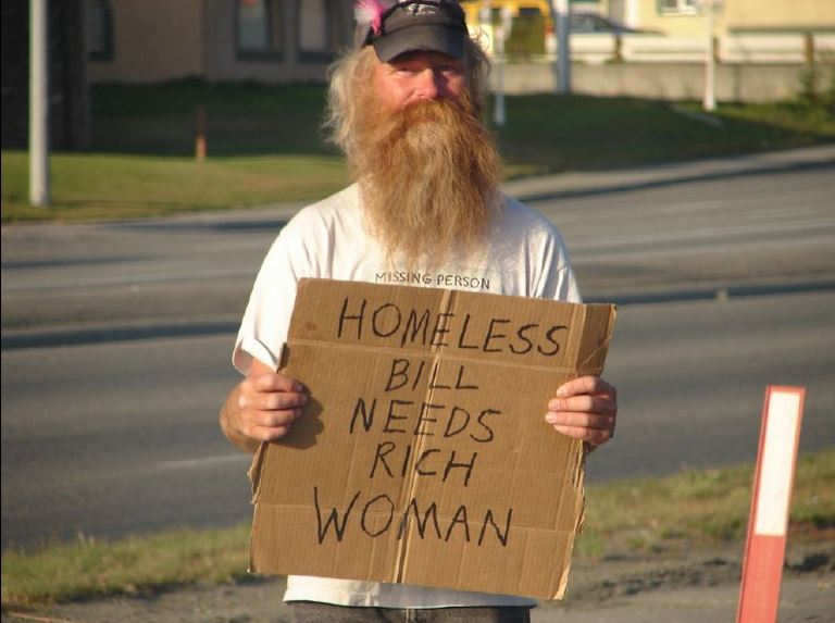 "photo of a homeless man holding a cardboard sign that says ""need rich woman"""