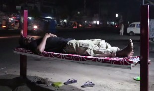 Billboards double as roadside beds for Pakistan's homeless laborers