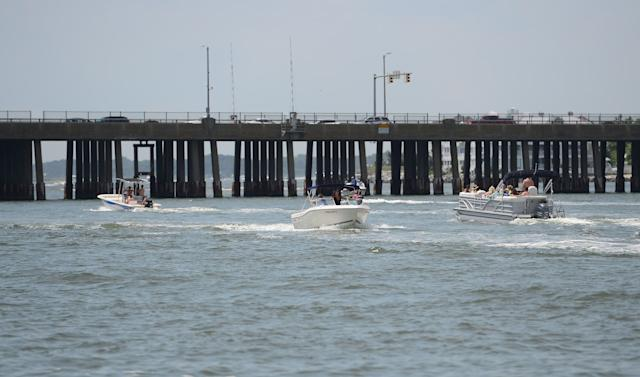 Boats travel from the bay to the ocean underneath the Route 50 bridge in Ocean City.