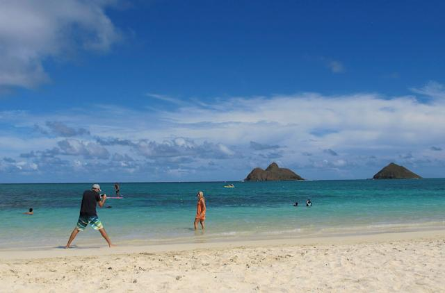 FILE - This Oct. 29, 2013 file photo shows tourists on Lanikai Beach in Kailua, Hawaii. Airbnb is pushing back against Hawaii's attempt to find tax delinquents by subpoenaing 10 years' worth of invoices, receipts and other records from the home-sharing platform's island hosts, calling it an unprecedented,